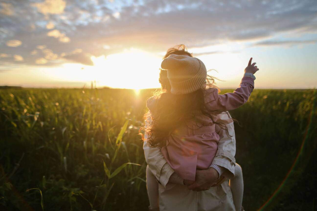 a mum carries her young daughter on her back through a field at sunset