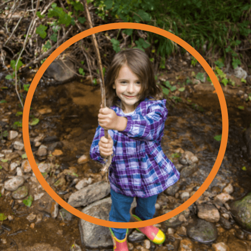 a girl in a blue and purple checked top plays with a rope swing in a brook.