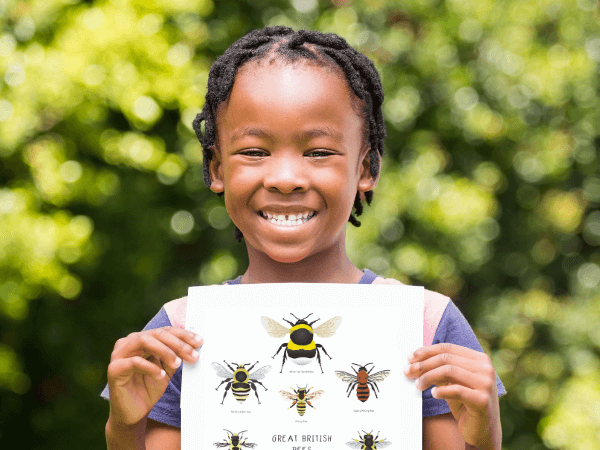 A beaming black little girl holds up the great British bee poster with augmented reality outside next to a backdrop of trees.