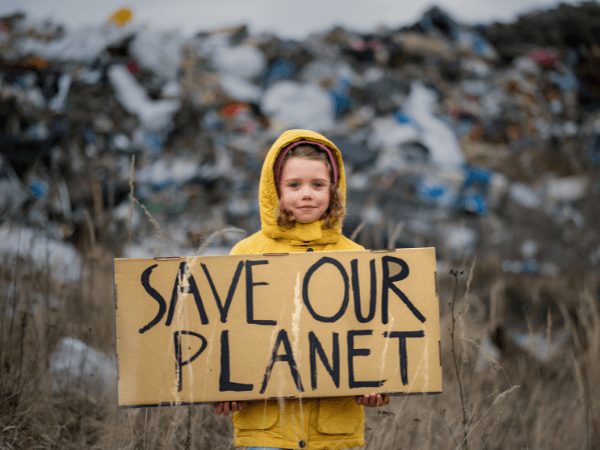 A girl in a yellow jacket holds a placard that says save our planet, she stands in front of a large rubbish pile.